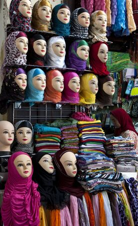 fez: A lady inspects the variety of colourful headscarves for sale in the Fez medina, Morocco.