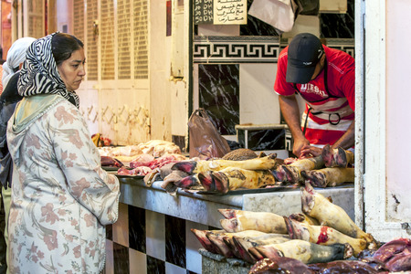 trotters: A lady looks at a selection of cow trotters at the Meknes medina in Morocco.