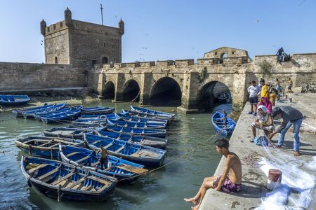 18th: A section of the fishing harbour with the fortress walls in the background at Essaouira in MoroccoThe present city of Essaouira was built during the 18th century by Mohammed III who wished to reorient his kingdom toward the Atlantic for security reasons.  Editorial