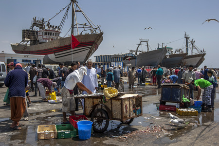18th century: A fishing trawler sits in dry dock as a fish monger sells fish at Essaouira in Morocco. The present city of Essaouira was built during the 18th century by Mohammed III who wished to reorient his kingdom toward the Atlantic for security reasons.