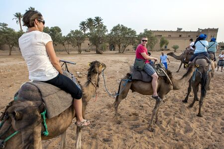 erg: Tourists ride camels at sunset at Merzouga, which lies on the edge of Erg Chebbi(the Sand Sea) in Morocco.