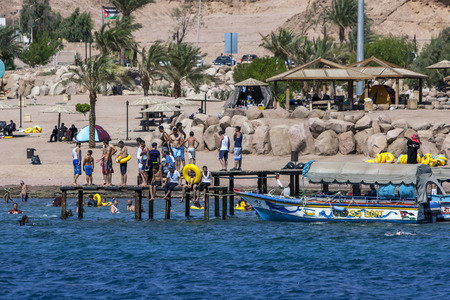 snorkelling: Visitors to Aqaba stand on a jetty as they prepare to cool of in the waters of the Gulf of Aqaba. Known to have excellent diving and snorkelling reefs, Aqaba attracts visitors from across Jordan as well as many from Saudi Arabia during the hot summer peri