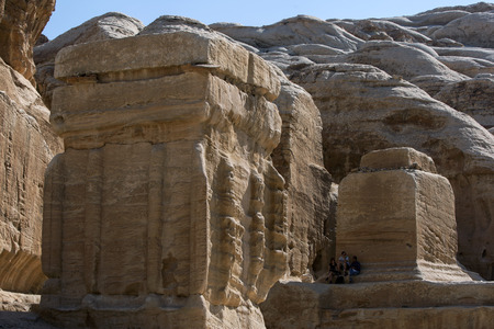 nabataeans: Tourists sit in the shade of giant carved boulders at the enterance of Petra in Jordan. Petra was possibly established  as early as 312 BC as the capital city of the Arab Nabataeans. Editorial