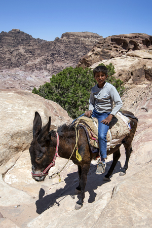 sacrificio: A Bedouin boy rides his donkey near the High Place of Sacrifice at Petra in Jordan. Petra was possibly established  as early as 312 BC as the capital city of the Arab Nabataeans.