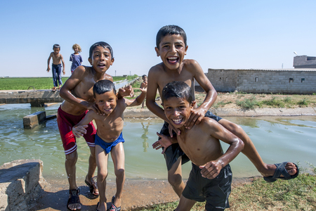 boys playing: Boys playing in an irragation channel next to the road from Urfa to Harran in eastern Turkey. With summer temperatures reaching upwards of 45 degrees for weeks on end the irrigation channels provide some relief for the locals. An unusual custom in this pa