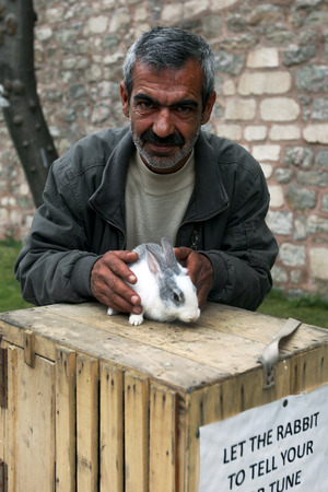 turkish man: A Turkish man with his fortune telling rabbit who amuses tourists in the Sultanahmet district of Istanbul in Turkey.