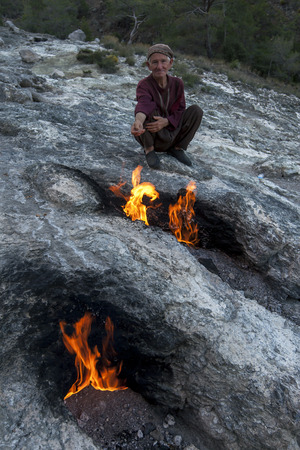 turkish man: A Turkish man sits beside the flaming rocks at Chimaera near Cirali on the Mediterranean coast of Turkey. The site, also known as Burning Rock, is located on Mt Olympos and the gas which continuously burns is methane based.