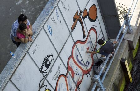 eminonu: A young couple relax on Galata Bridge at Eminonu in Istanbul in Turkey as a graffiti artist works below. Editorial