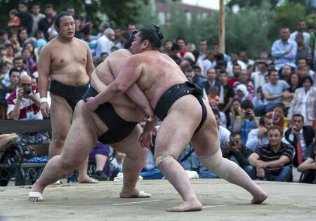 bout: Sumo wrestlers put on a exhibition bout for a curious audience at Edirne in Turkey. Editorial