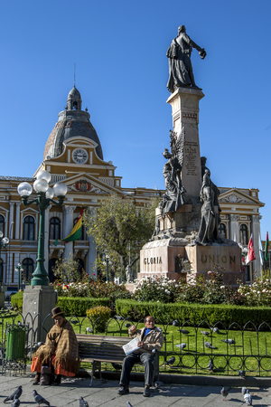 murillo: People sit on a park bench in Plaza Murillo. In the background stands the beautiful Legislative Palace in La Paz in Bolivia.