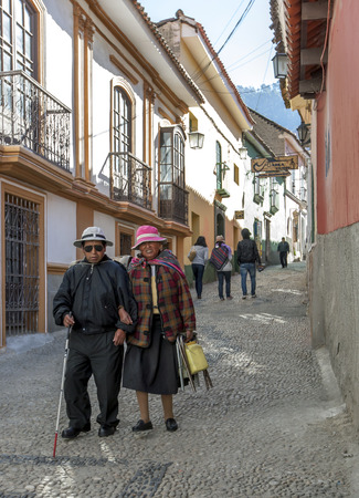 la paz: An elderly couple walk down a street in the old town section of La Paz in Bolivia.