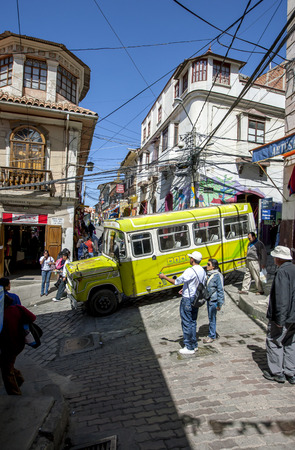 cerro: A bus drives down a steep and narrow street in Cerro Cumbre in La Paz in Bolivia. This suburb of La Paz is adjacent to the Witches Market and has a chaotic overhead wiring network.