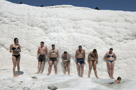 cliff face: Bathers stand along the travertines as the calcium carbonate rich spring water flows over the cliff face. The travertines, also known as Cotton Castle, are located above the town of Pamukkale in Turkey. Editorial