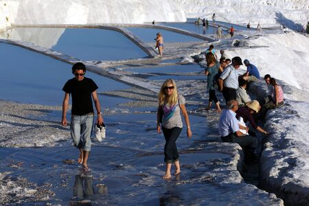 calcium carbonate: Tourists walking through the man-made baths built at Cotton Castle at Pamukkale in Turkey. Also referred to as travertines, the landscape has formed over thousands of years as a result of calcium carbonate rich water flowing over the mountain side.