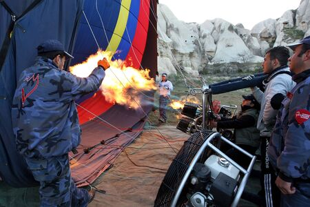 propane gas: Pilot Halis Aydogan, third from right, fires the nitrogen burners to create pressure within the balloon canopy before propane gas is used to heat the air within the balloon. The balloon will take from Rose Valley in Goreme in the Cappadocia region of Turk Editorial