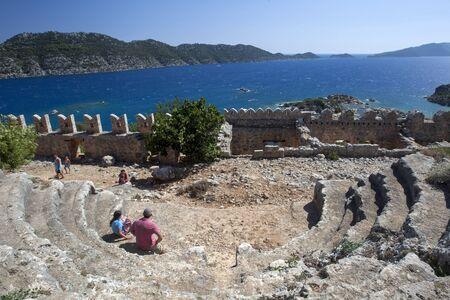 teatro antiguo: Los turistas se sientan en las ruinas del antiguo teatro dentro de la fortaleza de los cruzados en Simena. Simena se encuentra por encima del moderno pueblo de pescadores de Kalekoy situado en el Mar Mediterr�neo. Editorial