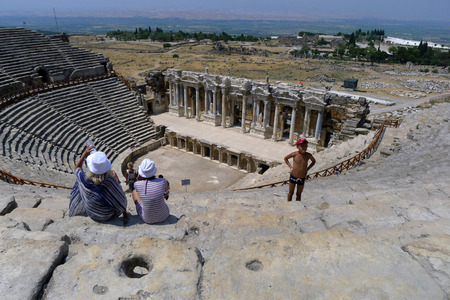 exceeding: Tourists sit in the spectacular ruins of the Roman Theatre at Hierapolis in Pamukkale in Turkey. It had a seating capacity exceeding 12,000 and was built in two stages by the emperors Hadrian and Septimius Severus. Hieropolis was established around 190 BC