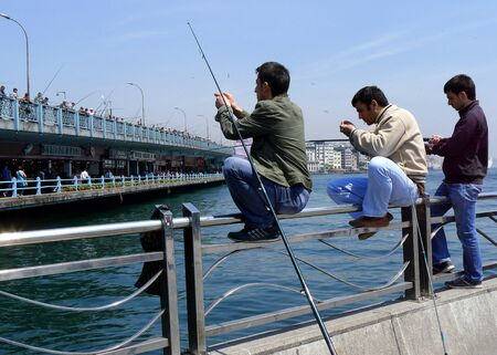 eminonu: Fishermen bait their hooks at Eminonu which sits on Golden Horn in Istanbul in Turkey. Galata Bridge in the background. Editorial