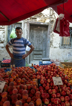 camii: A fruit seller stands with his produce including peaches and apples near Yesil Camii in Bursa in Turkey.