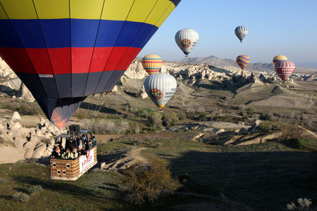 goreme: A spectacular sunrise view as a group of hot air balloons fly through Love Valley near Goreme in the Cappadocia region of Turkey.