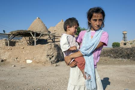 Une fille locale se tient tenant son jeune frère en face d'une maison de ruche dans l'ancienne ville de Harran dans le sud est de la Turquie. Harran est l'une des plus anciennes villes occupées en permanence dans le monde. Dès 800 avant JC, il était aussi un lieu de soleil, la lune et