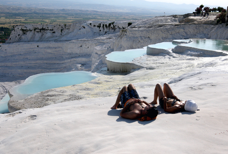 depositing: Visitors to Cotton Castle at Pamukkale relax on the travertines overlooking one of the most beautiful views in Turkey. The unique landscape was formed after calcium carbonate rich water flowed over the soil depositing calcium as it cooled. Editorial