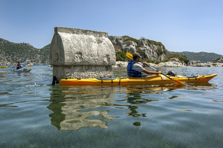 kayaker: A kayaker paddles past one of the sunken Lycian tombs at the ancient city of Simena. The area, which is today known as  Kalekoy, is situated on the Mediterranean Sea in Turkey.
