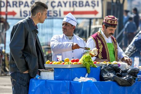 waits: A customer waits to be served his salad roll at a food cart next to Golden Horn at Karakoy in Istanbul in Turkey. Editorial