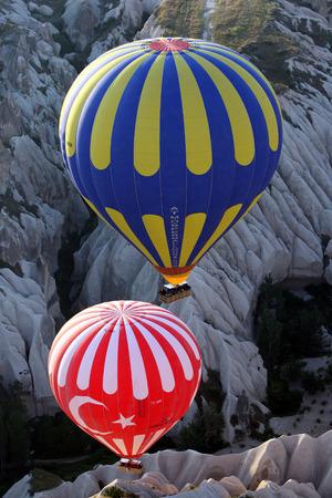 두 개의 뜨거운 공기 풍선 터키의 카파도키아 지역에서 일출 Goreme 근처 계곡 아래로 플 로트. 풍선이 골짜기에서 가장 좋은 위치를 차지하기 위해 많은 전화가 걸려 있습니다.