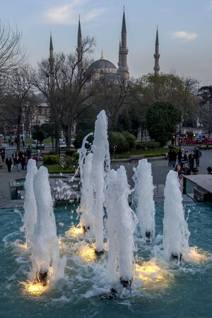 camii: A water fountain flows in the Sultanahmet Park. In the background is the magnificent Blue Mosque (Sultan Ahmet Camii) in the Sultanahmet district of Istanbul in Turkey.