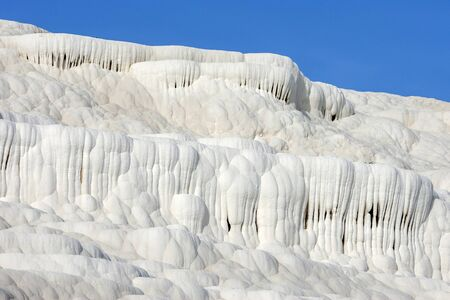 calcium carbonate: The late afternoon sun shines on the spectacular landscape at Cotton Castle (travertines) at Pamukkale in Turkey.
