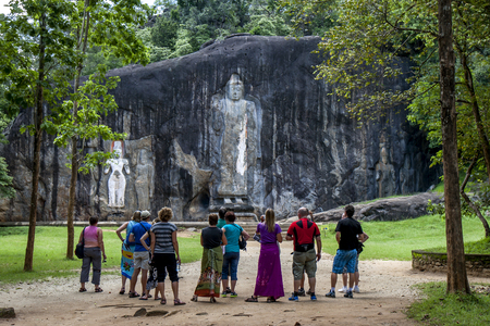 buddha sri lanka: Visitors admire the 15 metre high Buddha statue emerges from woodland at Buduruwagala, near Wellawaya in central Sri Lanka. Dating from the 10th century, this is the tallest standing Buddha statue in Sri Lanka.