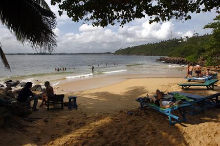 south coast: Visitors relax under the trees at Jungle Beach at Unawatuna on the south coast of Sri Lanka.