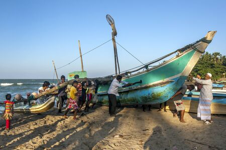 the east coast: Locals help push an outrigger canoe back onto the beach at Arugam Bay in the late afternoon. Arugam Bay is a fishing village on the east coast of Sri Lanka. Editorial
