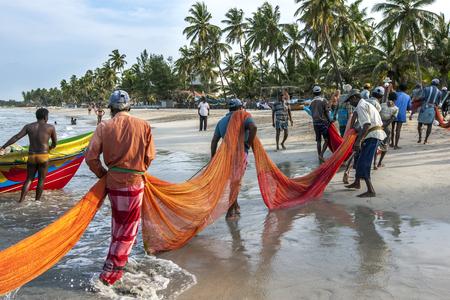 fishing nets: Fishermen pull in their fishing nets onto the beach at Uppuveli in Sri Lanka. Uppuveli is located on the east coast of Sri Lanka.