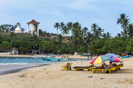 south coast: Tourists relax under beach umbrellas on Unawatuna beach on the south coast of Sri Lanka.In the background is a Buddhist Temple.