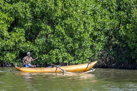 contend: A fisherman paddles past mangroves on Pottuvil Lagoon in Sri Lanka. With hazards such as crocodiles and elephants to contend with, the fishermen show no fear whilst fishing for sardines. Pottuvil lies on the central east coast of Sri Lanka.