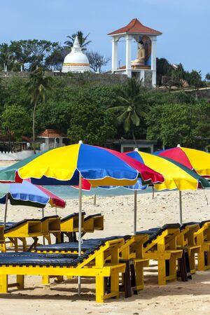 south coast: Beach umbrellas set up on Unawatuna beach on the south coast of Sri Lanka early in the morning. Stock Photo
