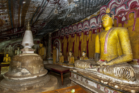 dagoba: The beautiful interior of Cave 4 at Dambulla Cave Temples which contains a small dagoba (left) as well as several seated Buddha statues including the one at right. Sri Lanka.