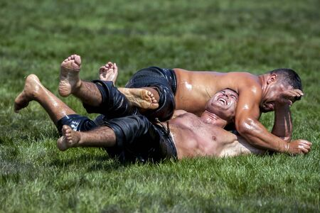 overpowered: A heavy weight wrestler is overpowered by his opponent during competition at the Elmali Turkish Oil Wrestling Festival in Elmali in Turkey. Editorial