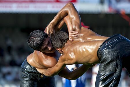 wrestlers: Middle weight wrestlers engaged in battle at the Elmali Turkish Oil Wrestling Festival in elmali in Turkey.