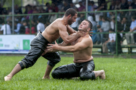 wrestlers: A wrestler grasps his opponent by the throat during a fierce battle at the Kagithane Turkish Oil Wrestling Festival in Istanbul in Turkey.
