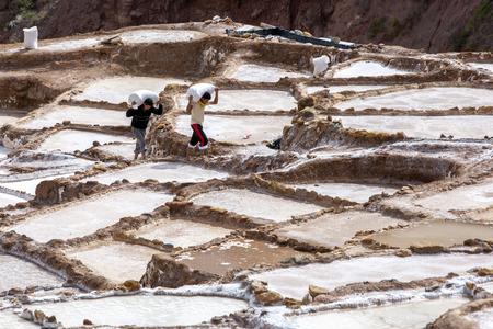 evaporacion: Los trabajadores llevan bolsas de sal recogidos de los estanques de evaporación de sal de Maras. Situado en el valle sagrado de los incas la región de Perú, a unos 40 kilómetros al norte de Cusco, los estanques han estado en uso desde la época de los incas.