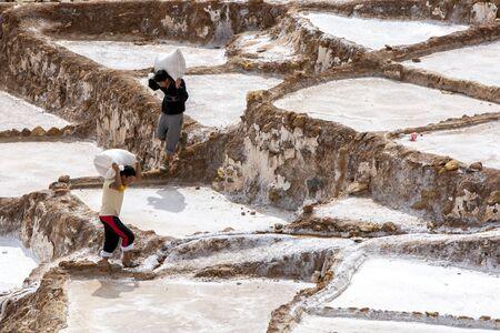 evaporacion: Los trabajadores llevan bolsas de sal recogidos de los estanques de evaporaci�n de sal de Maras. Situado en el valle sagrado de los incas la regi�n de Per�, a unos 40 kil�metros al norte de Cusco, los estanques han estado en uso desde la �poca de los incas.
