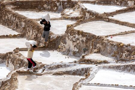 sacred valley of the incas: Workers carry bags of salt collected from the Maras salt evaporation ponds. Located in the Sacred Valley of the Incas region of Peru, some 40 kilometres north of Cusco, the ponds have been in use since the days of the Incas.