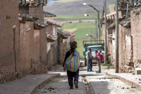 sacred valley of the incas: A Peruvian lady walks down a street in the town of Maras in the Sacred Valley of the Incas in Peru.