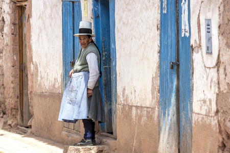 sacred valley of the incas: A Peruvian lady stands at the doorway to her home in the town of Maras in the Sacred Valley of the Incas in Peru.
