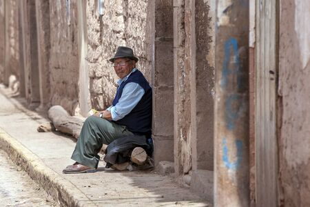sacred valley of the incas: A Peruvian man sits at the doorway to his home in the town of Maras in the Sacred Valley of the Incas in Peru.