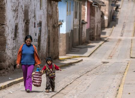 sacred valley of the incas: A Peruvian lady and child walk down a street in the town of Maras in the Sacred Valley of the Incas in Peru.