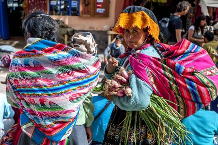 sacred valley of the incas: A colourfully dressed Peruvian lady holding a bunch of vegetables at the market in Pisac located in the Sacred Valley of the Incas in Peru.